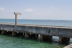 A ponte do cimento da passagem estende no mar imagem de stock