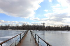 A ponte do ferro através do rio coberto com o gelo imagens de stock