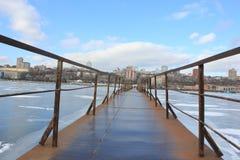 A ponte do ferro através do rio coberto com o gelo imagem de stock