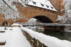 Ponte do ferro de Nuremberg nevado, Alemanha (Kettensteg), paredes velhas da cidade da cidade imagens de stock