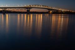 A ponte do porto de Auckland iluminou-se acima na noite imagens de stock royalty free