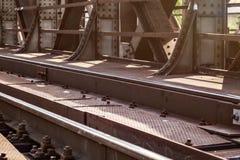 Ponte do trilho, detalhe em trilhas, placas de aço, grandes porcas - e - parafusos leves pelo sol imagens de stock