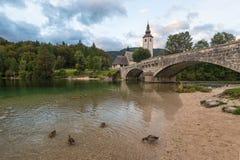 Ponte e chiesa di pietra nel villaggio di Ribchev Laz vicino alla l immagine stock libera da diritti