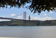 A ponte e o Cristo Rei em Tagus River depositam imagens de stock