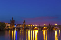 Ponte e riva di Charles con le riflessioni a Praga, repubblica Ceca durante l'ora del blu di alba immagini stock