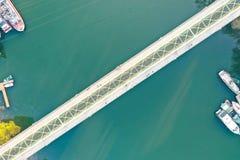 Ponte estreita longa que vai sobre um grande rio com os navios entrados na costa foto de stock royalty free
