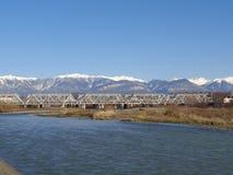 Ponte ferroviario attraverso il fiume, montagne innevate dietro Fotografia Stock Libera da Diritti