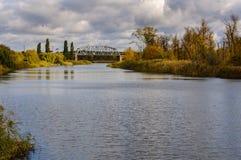 Ponte ferroviario sopra il fiume contro lo sfondo della foresta di autunno Fotografia Stock