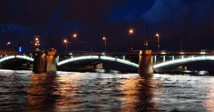 Ponte illuminato attraverso del fiume Neva sui precedenti del cielo notturno Fotografia Stock