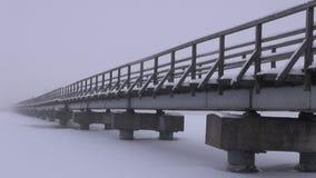 Ponte longa de madeira no gelo do lago no inverno e na névoa video estoque