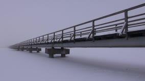 A ponte longa de madeira velha no lago nevado no inverno e a manhã enevoam-se video estoque