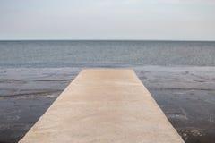 A ponte longa do cimento da perspectiva estende ao mar com s natural Fotos de Stock