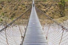 Ponte lungo con la donna di camminata, ponte del piede sopra il fiume della montagna, immagini stock