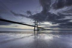 Ponte lungo sopra il Tago a Lisbona ad alba fotografia stock libera da diritti