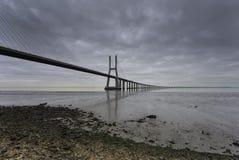 Ponte lungo sopra il Tago a Lisbona all'alba fotografie stock libere da diritti