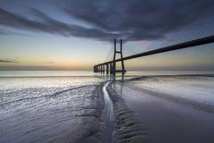 Ponte lungo sopra il Tago a Lisbona all'alba fotografia stock