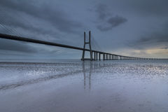 Ponte lungo sopra il Tago a Lisbona all'alba fotografia stock libera da diritti
