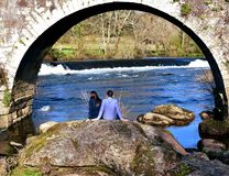 Ponte Maceira, Spain, 16 Feb 2019. A couple taking a break under a bridge. Rocks, river with waterfall and forest. stock photo