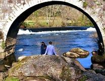 Ponte Maceira, Spanje, 16 Februari 2019 Een paar die een onderbreking nemen onder een brug Rotsen, rivier met waterval en bos stock foto
