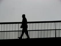 A ponte mostra em silhueta pedestres do tráfego Imagens de Stock