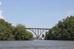 Ponte muito altamente arqueada sobre um rio largo imagem de stock