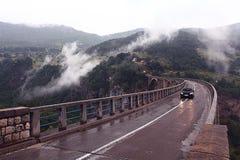 Ponte nella nebbia delle montagne Immagine Stock