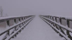 A ponte nevado de madeira e a manhã do inverno vazio enevoam-se vídeos de arquivo