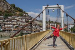 Ponte pedestre sobre o rio Lumi i Osumit que negligenciam as casas brancas medievais e menina de nivelamento do turista em um blo imagens de stock