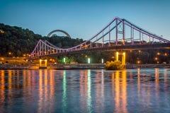 Ponte pedonale di Kiev alla notte illuminata dalle luci multicolori Immagini Stock