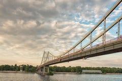 Ponte pedonale sopra il fiume al tramonto Immagini Stock