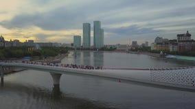 Ponte pedonale sotto forma di pesce sopra il fiume di Esil, Astana video d archivio