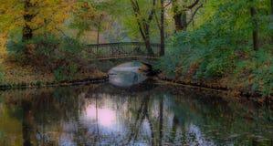 Ponte romantico nel parco Alberi variopinti di autunno Fogli di caduta fotografia stock libera da diritti