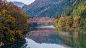 Ponte rosso al fiume di Tadami Fotografie Stock