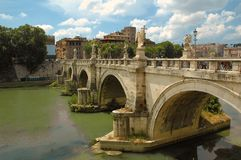 Ponte Sant Angelo over river tiber in Rome. Banks of river Tiber and white marble angels on the Ponte Sant Angelo in Rome stock photos