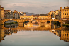 Ponte Santa Trinita Bridge Florence. Florence, Italy-June 12, 20015.View of the Ponte Santa Trinita Bridge, iwith tourists in wooden boat,n the late afternoon Royalty Free Stock Photos