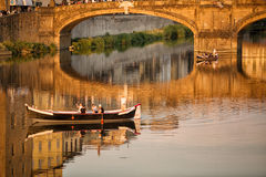 Ponte Santa Trinita Bridge Florence. Florence, Italy-June 12, 20015.View of the Ponte Santa Trinita Bridge, iwith tourists in wooden boat,n the late afternoon Royalty Free Stock Images