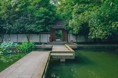 Ponte sobre a lagoa que conduz a uma entrada sob árvores, em um jardim chinês, perto do lago ocidental, Hangzhou, China imagem de stock