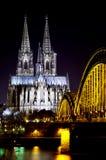 Ponte sobre o rio de Rhine com a catedral de Colónia no fundo na noite Colónia, Alemanha Foto de Stock Royalty Free