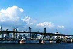 Ponte sobre a opinião de céu azul do rio e da nuvem da skyline e do arranha-céus de Banguecoque foto de stock royalty free