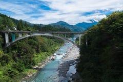 Ponte sopra il fiume in alpi giapponesi Fotografia Stock Libera da Diritti