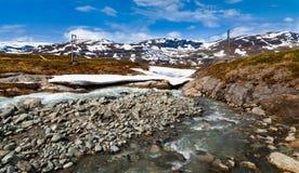 Ponte sopra un fiume selvaggio della montagna, montagne nevose nel fondo Fotografia Stock