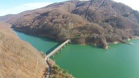 Ponte sopra un lago nelle montagne, vista aerea video d archivio