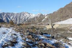 Ponte sospeso attraverso il fiume fra le montagne, Altai, Russia di Katun Fotografia Stock