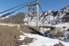 Ponte sospeso attraverso il fiume fra le montagne, Altai, Russia di Katun Fotografie Stock Libere da Diritti