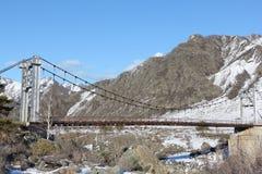 Ponte sospeso attraverso il fiume fra le montagne, Altai, Russia di Katun Immagini Stock Libere da Diritti