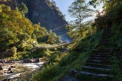 Ponte sospeso sopra il fiume del canyon della montagna Immagine Stock
