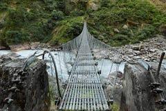 Ponte sospeso sopra il fiume ruvido della montagna immagini stock