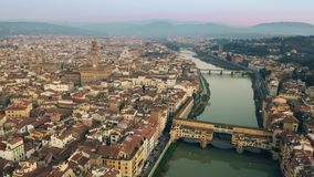 Crowded Ponte Vecchio bridge in the evening, aerial view. Florence, Italy stock video footage