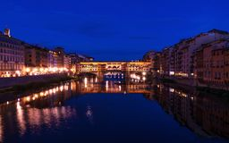 Ponte Vecchio bridge in Florence at night time with city lights reflecting in Arno river. Royalty Free Stock Image