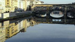 Ponte Vecchio in Florence. Camera moves from reflections on river to bridge stock footage